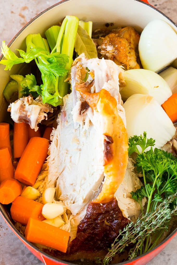 A turkey carcass in a pot with vegetables.