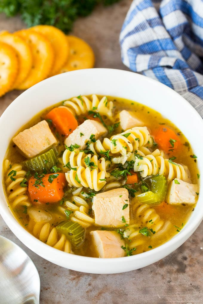 A bowl of turkey noodle soup served with parsley and crackers.