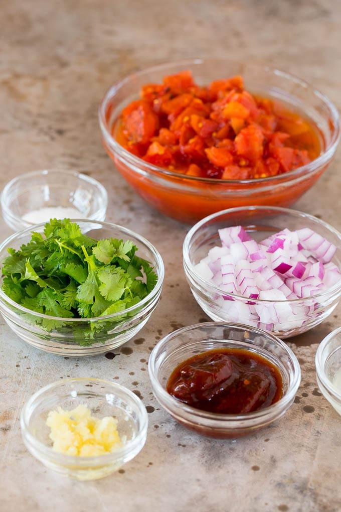 Bowls of tomatoes, cilantro, onions and seasonings.