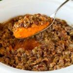 A spoon serving up a portion of crock pot sweet potato casserole.