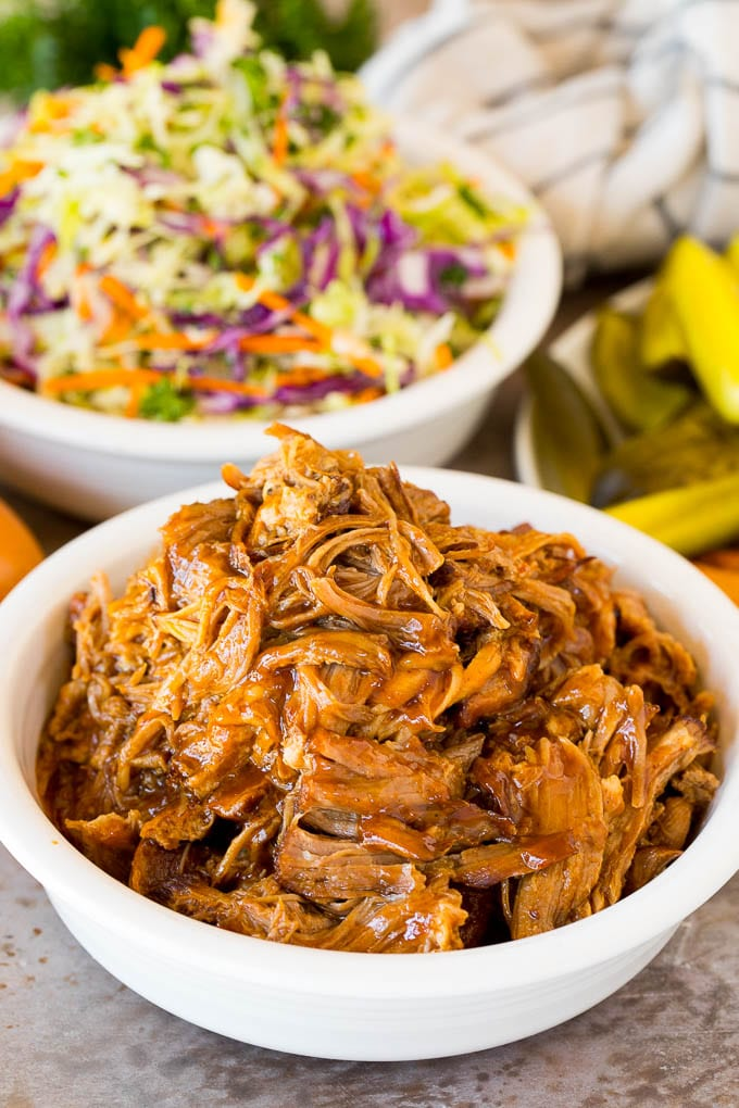A bowl of Instant Pot pulled pork served with coleslaw and pickles.