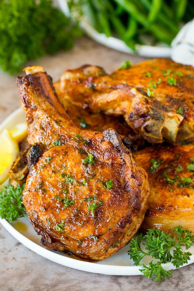 A plate of air fryer pork chops garnished with parsley.