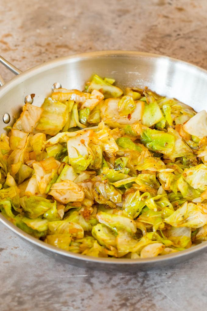 Sauteed cabbage with seasonings in a skillet.