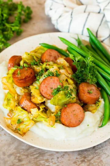 A plate of cabbage and sausage served over mashed potatoes with green beans.