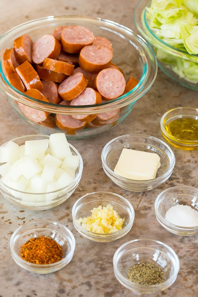 Bowls of ingredients including chopped cabbage, sliced sausage and seasonings.