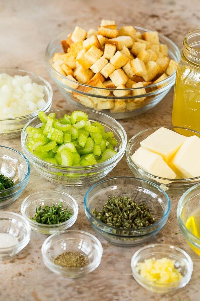 Bowls of bread cubes, vegetables, herbs and seasonings.