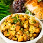 A bowl of crock pot stuffing topped with fresh herbs.