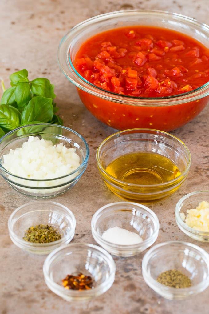 Bowls of ingredients including tomatoes, herbs and seasonings.