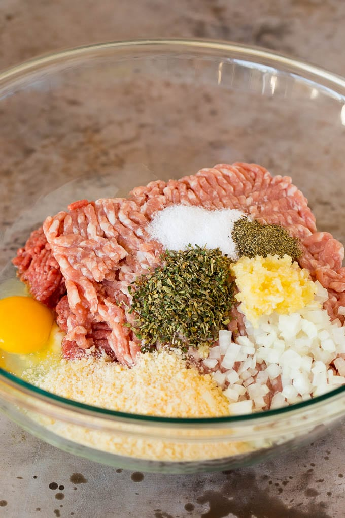 Ground beef, pork and seasonings in a mixing bowl.