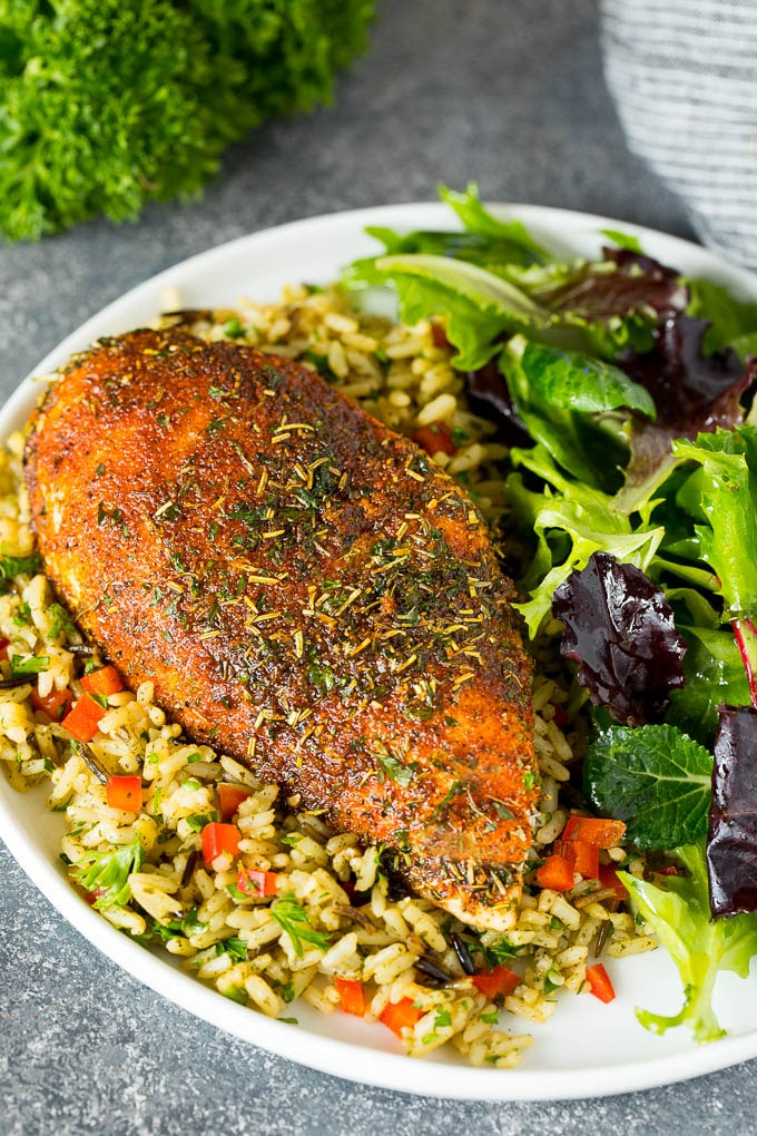Chicken seasoning on a cooked chicken breast, served with rice and salad.