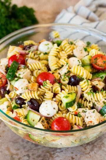 A bowl of chicken pasta salad with tomatoes, cucumbers and cheese.