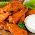 Air fryer chicken wings coated in buffalo sauce and served with ranch and celery.