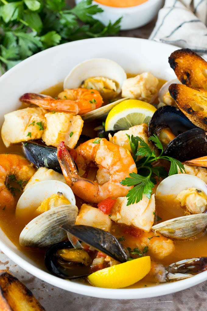 A serving bowl of bouillabaisse with shrimp, clams and fish.