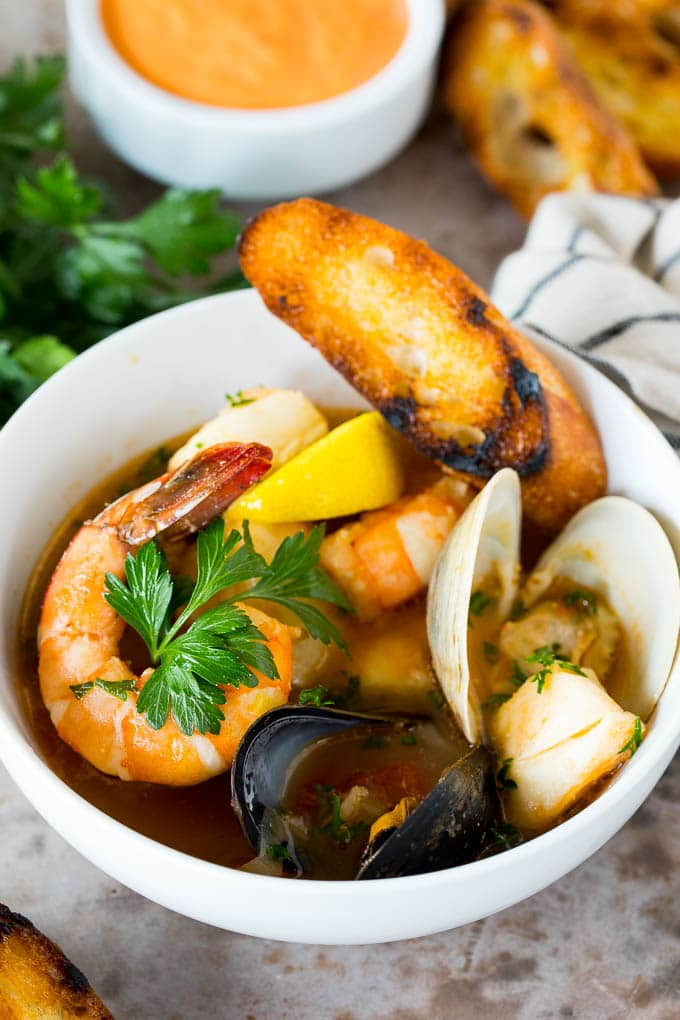 A bowl of bouillabaisse served with toasted bread slices.